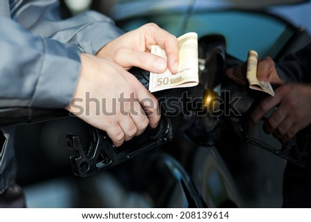 Fueling up a car at the gas station - stock photo
