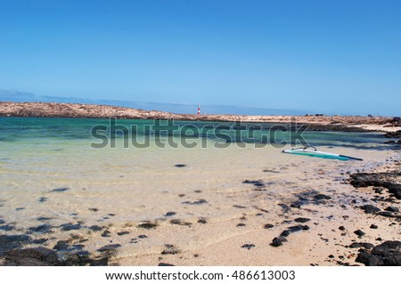 Fuerteventura: a windsurf in Caleta de la Adana and El Toston Lighthouse on September 3, 2016. Caleta de la Adana is a little bay near El Toston Lighthouse, whose original structure was opened in 1897
