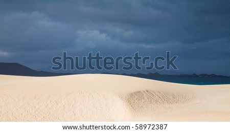 Fuerteventura, Corralejo sand dunes nature park, sand dunes in the sun, overcast ocean and Lanzarote in the background