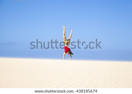 Fuerteventura sand dunes in the north of the island, teenage boy in red t-shirt making handstands - stock photo