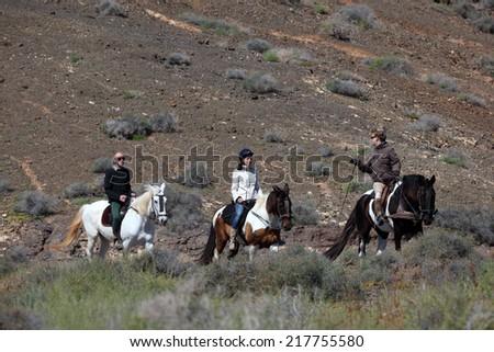 FUERTEVENTURA, SPAIN - MAR 29: Group of people riding through the landscape of Fuerteventura.  March 29, 2011 in Canary Island Fuerteventura, Spain  - stock photo