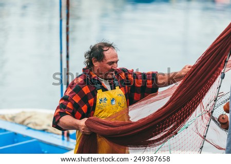 FUERTEVENTURA, SPAIN - OCTOBER 27: Traditional fishermen unloading catch in the port of Morro Jable in Canary Islands. October 27, 2014 in Morro Jable, Fuerteventura, Spain - stock photo