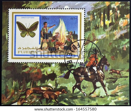 FUJEIRA - CIRCA 1972: A stamp printed in Fujeira shows boy scouts and ornithoptera, circa 1972  - stock photo