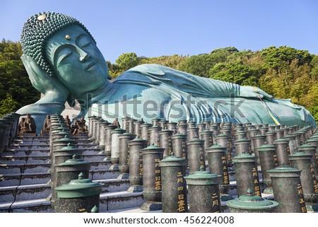 FUKUOKA, JAPAN-May 30, 2016: The bronze statue of reclining Buddha state at Nanzoin Temple in Sasaguri, Fukuoka, Japan.This is the bigest lying statue in the world. - stock photo