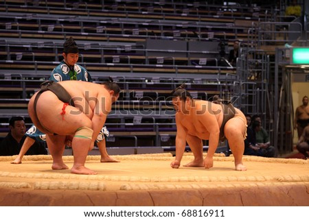 FUKUOKA, JAPAN - NOVEMBER 19: Small and big sumo wrestlers ready to engage in the arena of the Fukuoka Tournament on November 19, 2010 in Fukuoka, Japan. - stock photo