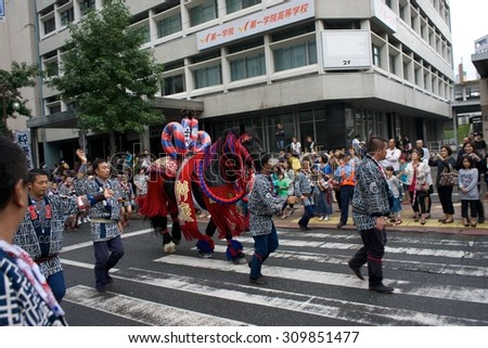 FUKUOKA, JAPAN - OCTOBER 21, 2014: Japanese people wearing traditional cloth march on the street with horse.