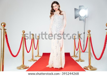 Ful llength portrait of a charming woman walking on red carpet  - stock photo