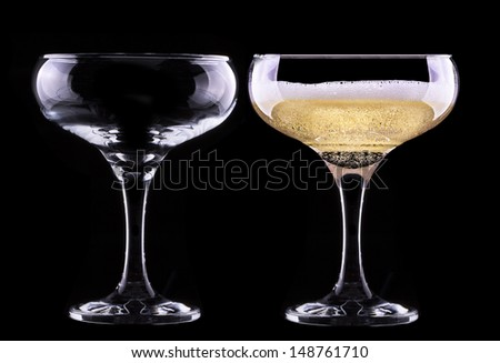 full and empty glass of champagne isolated on black background - stock photo