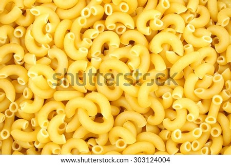 Full background of dry uncooked macaroni pasta - stock photo