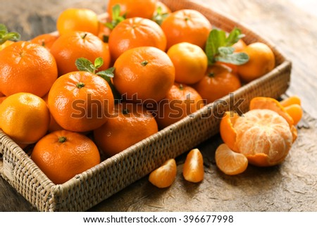 Full basket of fresh, delicious tangerines on the rustic table, close up - stock photo