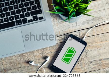 Full battery mobile phone in a desktop. - stock photo