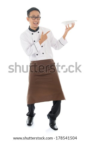 Full body Asian chef holding and pointing to an empty plate, standing isolated on white background. - stock photo