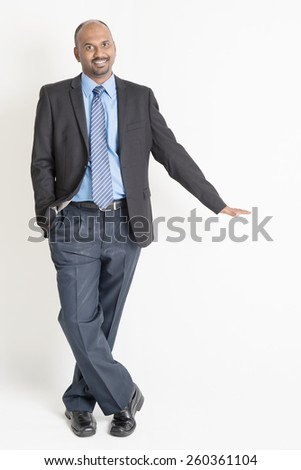 Full body Asian Indian businessman putting hand on invisible banner over plain background - stock photo