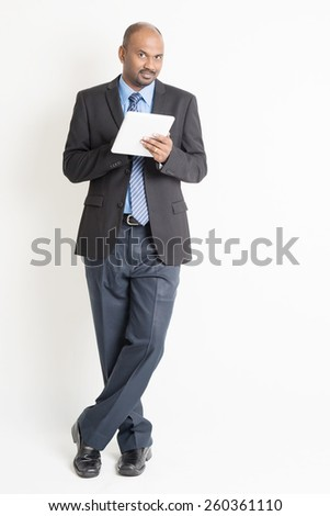 Full body Asian Indian businessman using digital tablet pc standing over plain background - stock photo