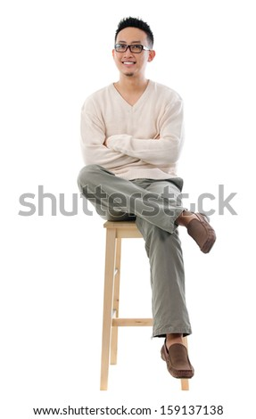 Full body Asian male sitting on a chair isolated over white background - stock photo