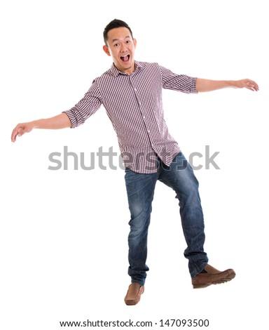 Full body Asian man walking carefully, try to balance himself, isolated on white background. Asian male model. - stock photo