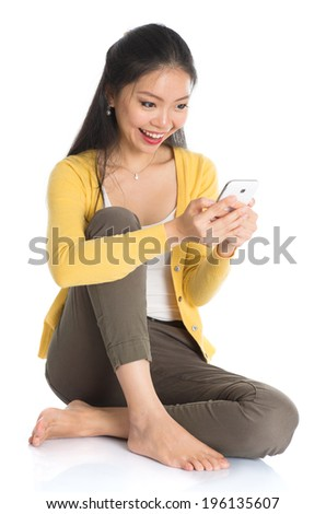 Full body Asian woman in yellow blouse texting with smartphone, seated on floor, isolated on white background