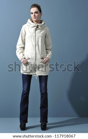full body attractive young woman in jeans on blue background