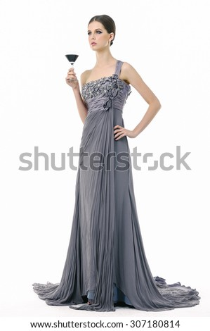 Full body beautiful bridge in dress holding cup in her hands posing in studio - stock photo