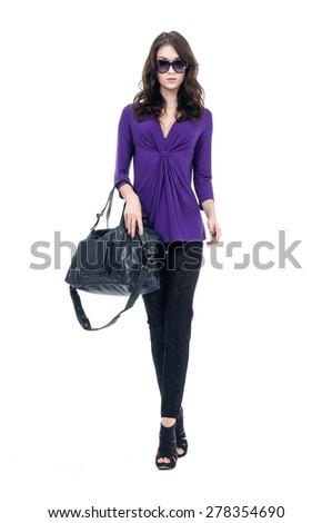 Full body beautiful girl with bag walking in studio - stock photo
