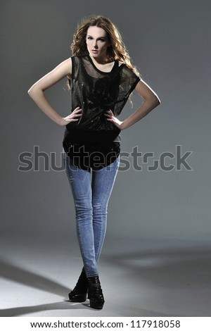 Full body beautiful young woman in jeans posing light background - stock photo