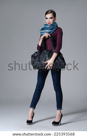 Full body beauty girl with scarf holding purse posing gray background - stock photo