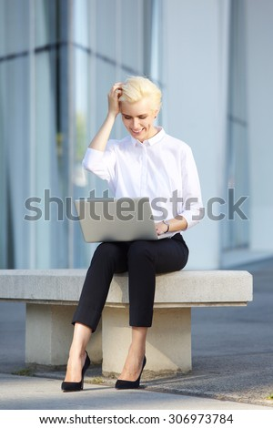Full body cheerful young business woman using laptop outside - stock photo