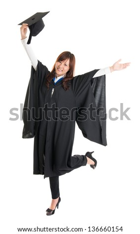 Full body excited Asian female student in graduation gown hands raised open arms jumping isolated on white background - stock photo