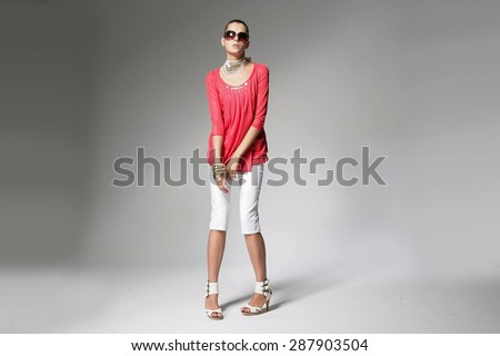 Full body fashion girl fashion model posing with sunglasses on gray background - stock photo
