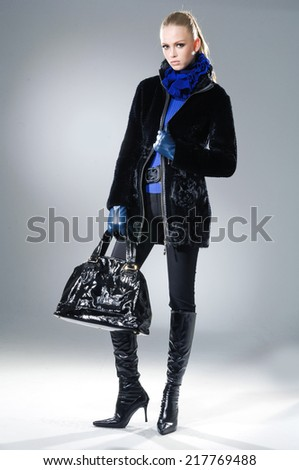Full body fashion model in autumn/winter clothes holding handbag posing on light background - stock photo