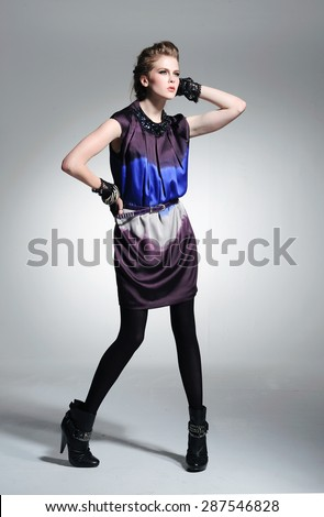 Full body fashion model in fashion dress posing on light background  - stock photo