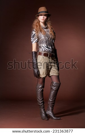 Full body fashion model in modern clothes with hat posing in the studio