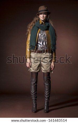 Full body fashion model in modern clothes with scarf posing in the studio