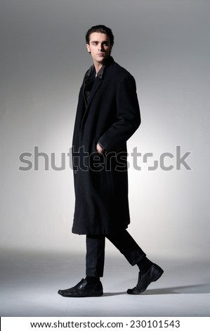 Full body Fashion Shot of a young business man in coat on light background