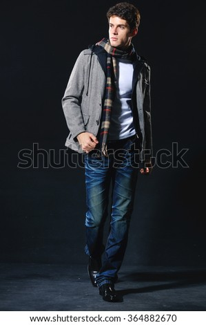 Full body Fashion Shot of a young man a professional model posing in studio