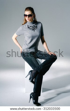 Full body fashion shot of girl with sunglasses sitting cube in light background  - stock photo