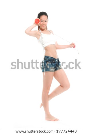 Full body fit young woman with measure tape ,healthy lifestyle concept. Woman hold slice grapefruit in hand.