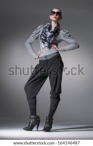 Full body High fashion model in scarf wearing sunglasses posing in the studio
