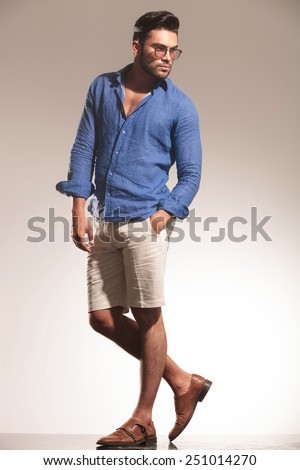 Full body image of a handsome young casual man looking away from the camera while holding one hand in his pocket. - stock photo