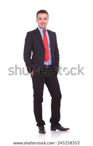 Full body image of a young business man smiling at the camera while holding both hands in his pocket.