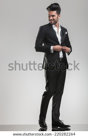 Full body image of an elegant young man closing his tuxedo, smiling while looking away from the camera. - stock photo