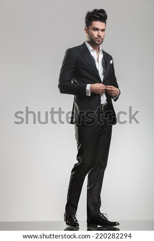 Full body image of an handsome young man looking away from the camera while closing his tuxedo.  - stock photo