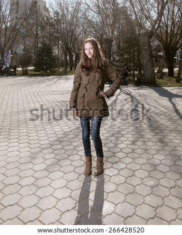 Full body image of cute young women posing outdoors in city park smiling in casual wear. A lot of copyspace on the pavement. Toned colorized stylized film photo look. - stock photo