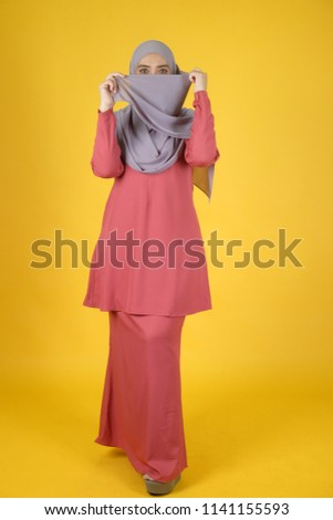 Full body image of Muslim women with yellow background. Studio shot