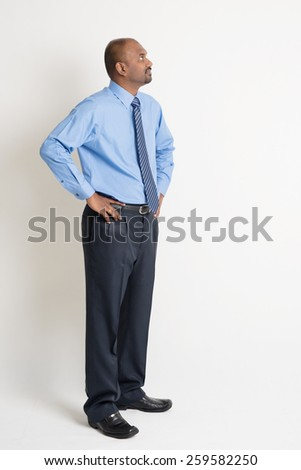 Full body Indian businessman hand on waist looking up at blank copy space, standing on plain background with shadow. - stock photo