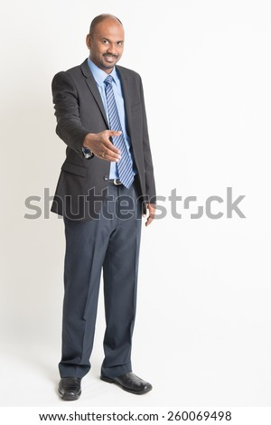 Full body Indian businessman offering hand shake looking at camera, standing on plain background. - stock photo