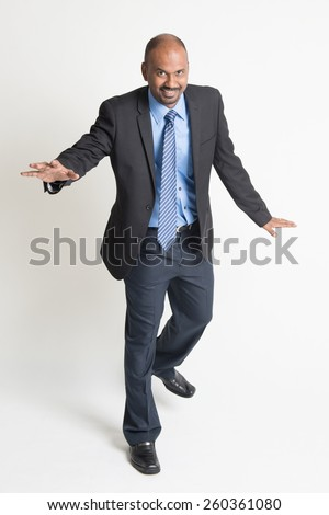 Full body Indian businessman walking balance , front view on plain background. - stock photo