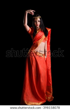 Full body Indian girl in red sari costume standing isolated on black background. Beautiful Indian girl in traditional Indian sari. beautiful indian woman wearing traditional sari studio portrait.