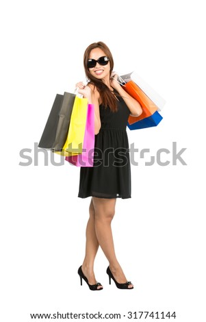Full body isolated on white profile of classy Asian female shopper, shopaholic in black dress and sunglasses flinging shopping bags over her shoulders ready to shop while looking at the camera - stock photo
