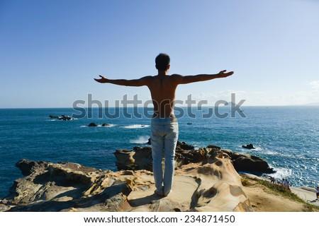 Full body man on beach doing yoga - stock photo